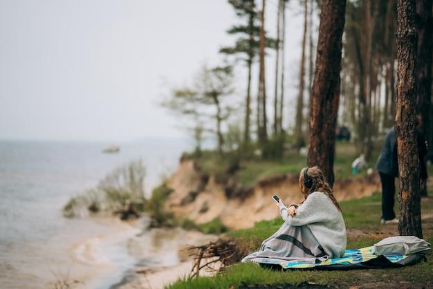 Молодая женщина сидит на берегу небольшого озера возле леса