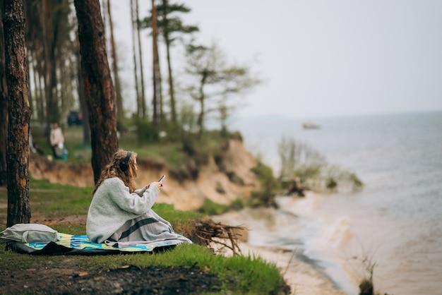 若い女性が森の近くの小さな湖のほとりに座っています