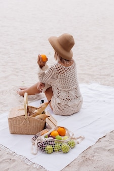若い女性が麦わら帽子とピクニックバスケットと白いニットの服でタオルの上に座っています