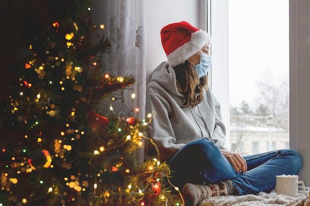 Молодая женщина сидит на окне в украшенном доме на рождество, разбирается в окне, женщина в медицинской стерильной маске