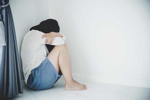 Молодая женщина, сидящая в одиночестве и подавленная. женщина депрессии сидит на полу, жестокое обращение и люди концепции