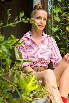 庭の小屋に座っている若い女性。