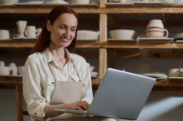 Молодая женщина сидит за ноутбуком в гончарной мастерской
