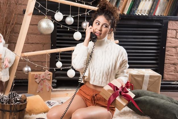 푹신한 카펫에 앉아서 전화로 말하는 젊은 여성