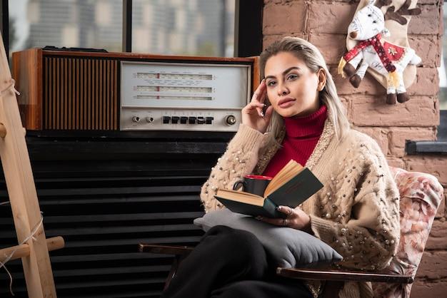 Молодая женщина сидит с книгой и пьет кофе
