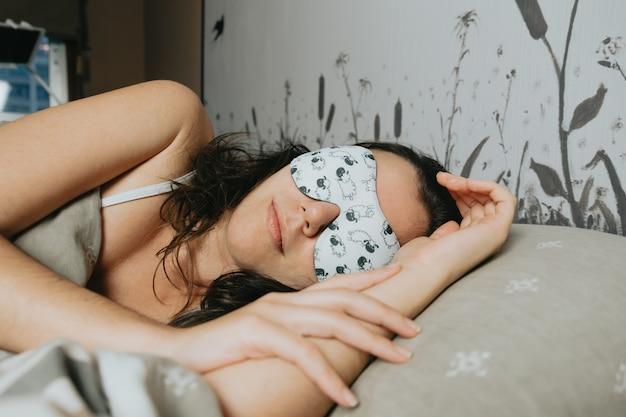 Молодая женщина спит на кровати с белой маской для сна