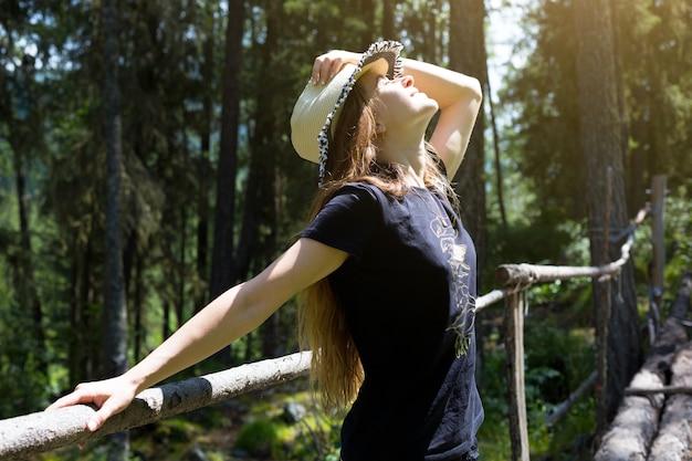 若い女性は笑顔で森の背景に彼女の手で彼女の頭に帽子をかぶっています