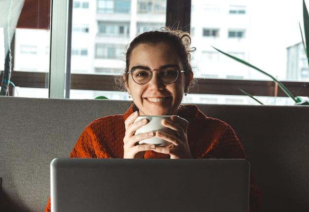 Молодая женщина улыбается перед своим ноутбуком на диване, держа чашку кофе
