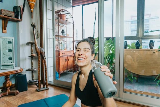 自宅でフィットネスやヨガをしながら水を飲みながら笑っている若い女性