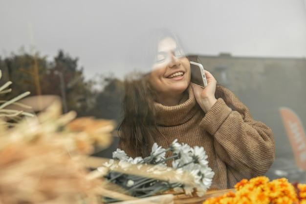 한 젊은 여성이 전화 통화를 하고 창에서 거리를 바라보고 있습니다.