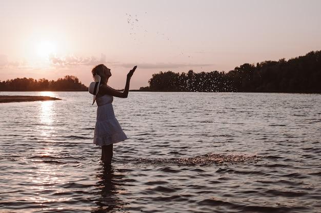 젊은 여자가 물을 튀긴다. 여름 드레스를 입은 날씬하고 아름답고 행복한 금발과 일몰을 배경으로 강가에 서서 손을 들고 있는 밀짚모자의 사진.