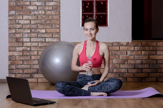 Молодая женщина-спортивный блогер отдыхает после тренировки онлайн, пьет воду из пластиковой бутылки на коврик для йоги. домашний фитнес