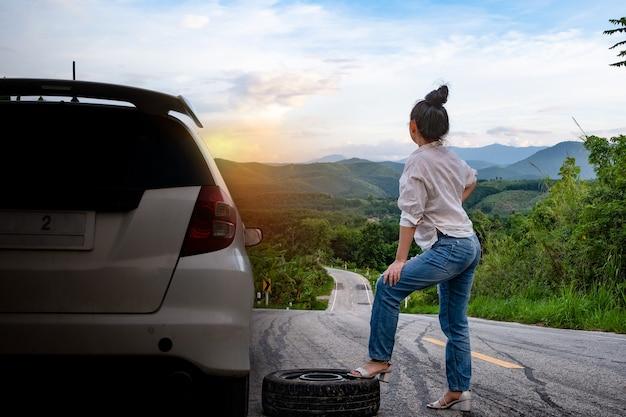 公道で助けを求めるために車の近くに立っている若い女性
