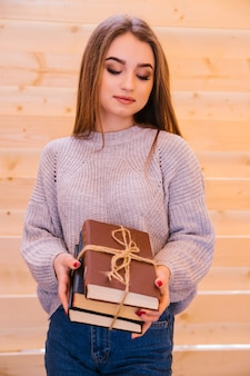 Молодая женщина стоит и держит в руках стопку книг. книги, перевязанные шнурком. девушка - студентка, готовится к вузу или экзамену.
