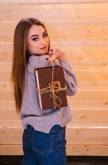 Молодая женщина стоит и держит в руках стопку книг.