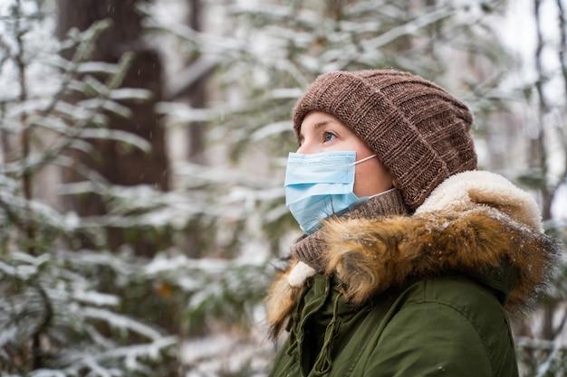 雪が降る冬の森に若い女性が立って、雪がどのように降るのかを見る