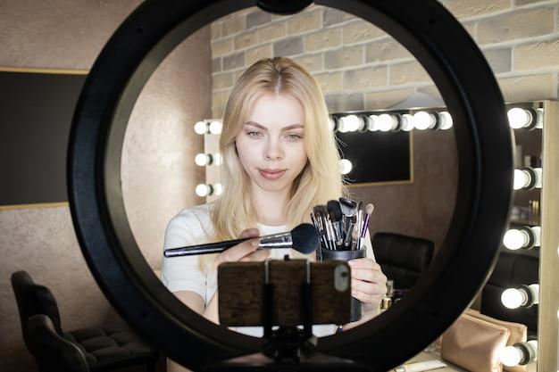 Молодая женщина стоит перед кольцевой лампой и проводит онлайн-курсы по нанесению макияжа.