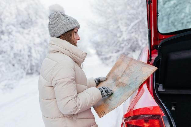 赤い車の横に立っている若い女性が地図を手に持っています。旅行のコンセプト。