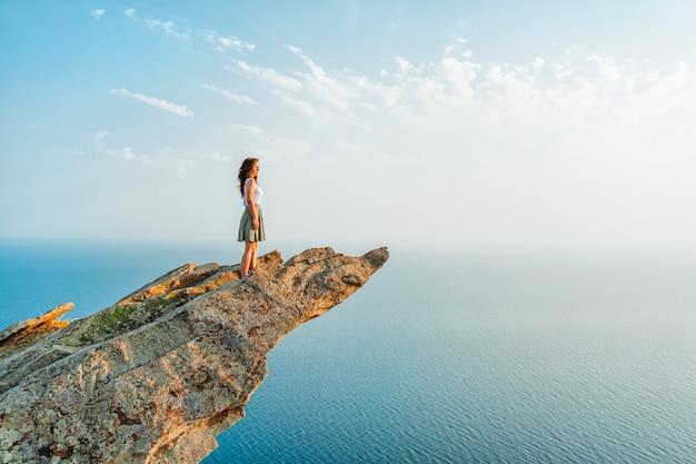 한 젊은 여성이 하늘을 배경으로 바다 위의 그림 같은 가파른 절벽에 서 있다