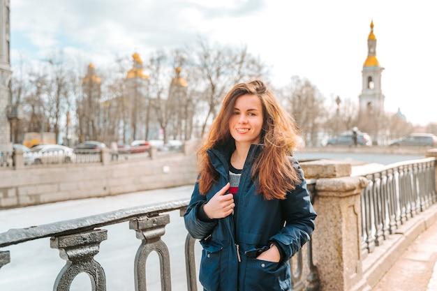 サンクトペテルブルクの堤防に立っている若い女性が春先に古い建物を眺める