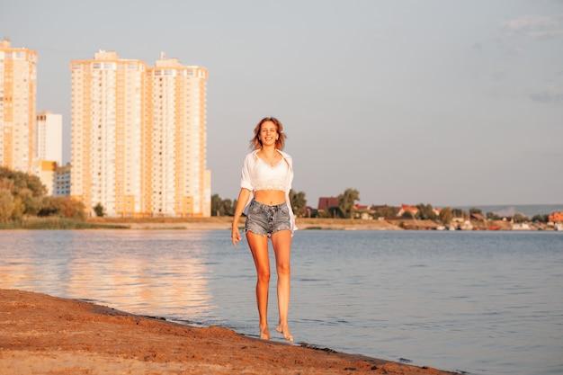 若い女性が川のほとりに立って、白いシャツを着た幸せな金髪とデニムのショートパンツが笑う...