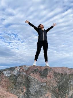 若い女性が腕を上げて山の頂上に立っています