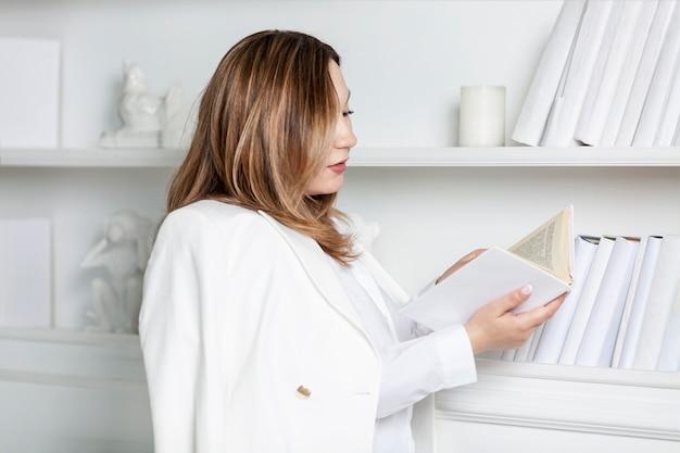 젊은 여자는 책장으로 책을 의미합니다. 흰 셔츠와 재킷에 웃는 갈색 머리. 교육과 지식. 세련된 인테리어.
