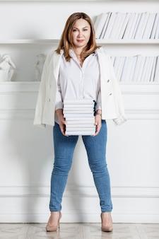 젊은 여자는 책장으로 책을 의미합니다. 흰 셔츠, 재킷과 청바지에 웃는 갈색. 교육과 지식. 전체 높이. 세로. 세련된 인테리어.