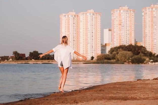 若い女性が川と街のほっそりした美しさを背景に背を向けて立っています...