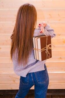 Молодая женщина стоит к нему спиной, держа стопку книг. книги, перевязанные шнурком. девушка учится, готовится к вузу или к экзамену.