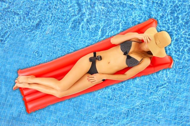 Молодая женщина загорает на красном матрасе в бассейне