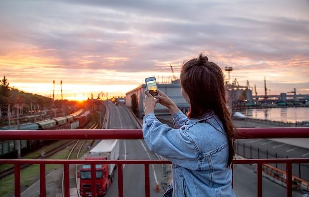 若い女性が携帯電話で橋から美しい夕日の写真を撮ります。