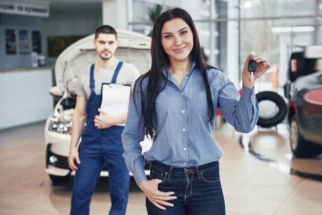 젊은 여성이 자동차 서비스 센터에서 자동차를 가져옵니다. 그녀는 일이 완벽하게 이루어지기 때문에 행복하다