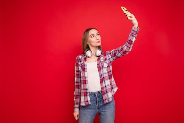 Молодая женщина делает селфи в наушниках на красном фоне