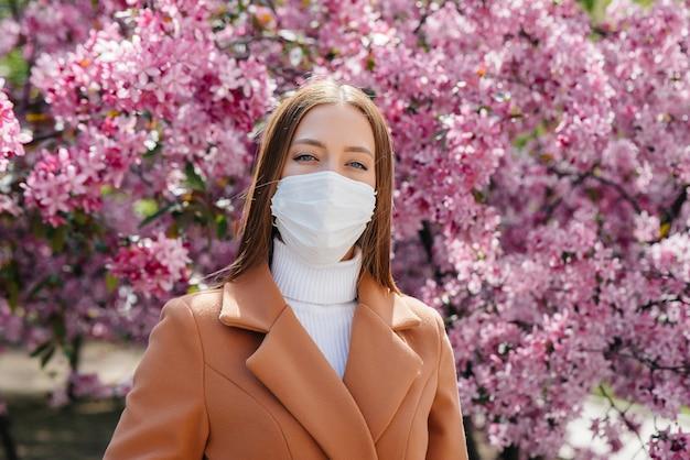 Молодая женщина снимает маску и глубоко дышит после окончания пандемии в солнечный весенний день.