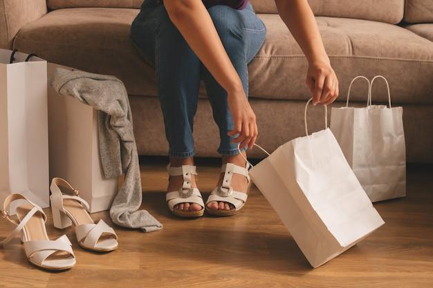 소파에 앉아있는 동안 젊은 여성이 가방에서 구매를 꺼냅니다.