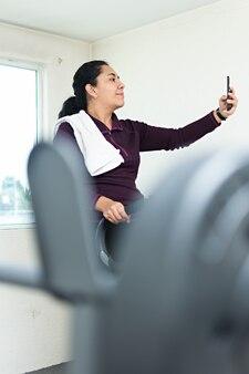 어깨에 수건을 메고 운동하는 동안 체육관에서 셀카를 찍는 젊은 여성