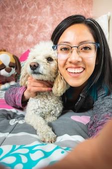 침실에서 자신과 작은 강아지의 셀카를 찍는 젊은 여성