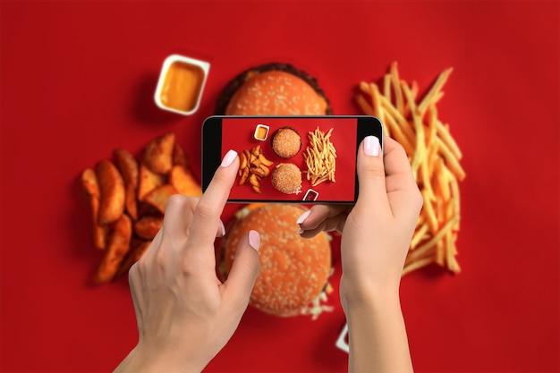 스마트폰으로 음식 사진을 찍고 모바일 카메라로 식사를 촬영하는 젊은 여성. 소셜 네트워크용으로 제작되었습니다. 상위 뷰 휴대 전화