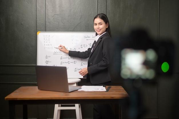 若い女性教師は、検疫、オンライン教育、遠隔教育の概念の間にオンラインレッスンを記録するためにカメラを使用しています。