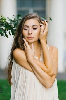 젊은 여성이 손으로 얼굴을 만집니다. 배려와 자기애의 개념