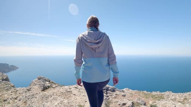 젊은 여성 여행자는 끝없는 바다가 내려다보이는 가장 높은 절벽을 올라갔습니다. 그녀는 팔을 옆으로 벌리고 아름다운 경치를 즐깁니다. 조용하고 숨이 멎을 듯한 풍경. 4k uhd