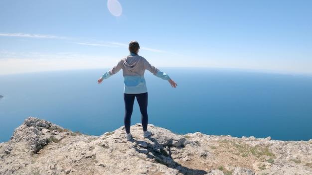 若い女性旅行者が腕を横に広げ、岩の上の海を見ています。アクティブなレクリエーションと旅行のコンセプト。カメラは女性、4kuhdの周りを動きます。