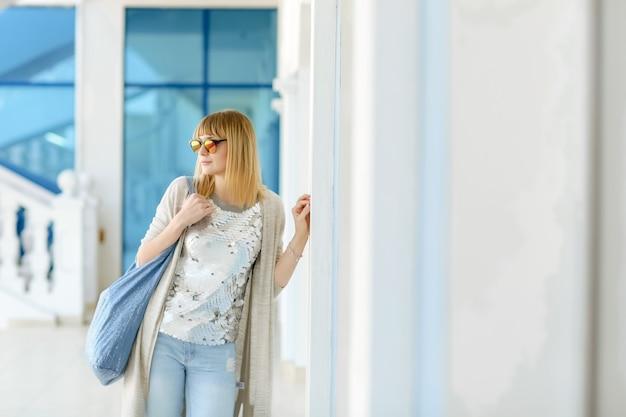 若い女性が快適な服を着て旅行し、白い建物の近くに立っています。