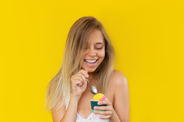 노란색 배경에 아이스크림이 든 크림 그릇을 들고 셔벗을 시도하는 젊은 여성