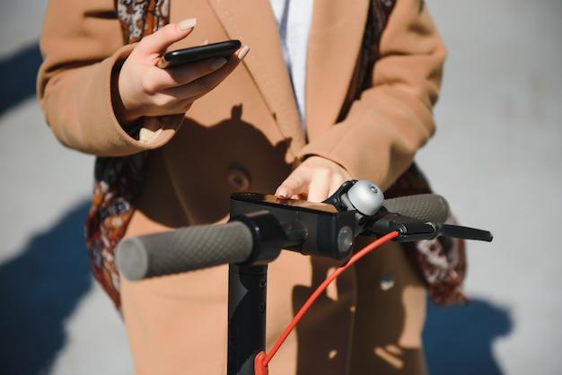 Молодая женщина открывает электронный самокат с помощью мобильного телефона
