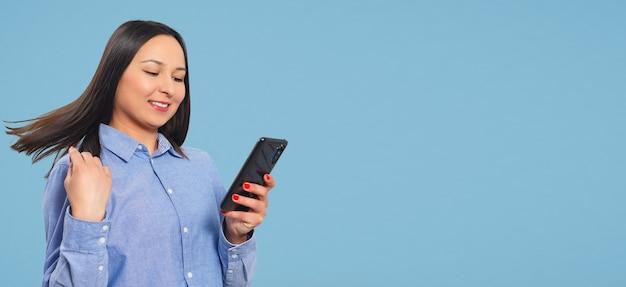 Молодая женщина использует смартфон на синем фоне. с copyspace.