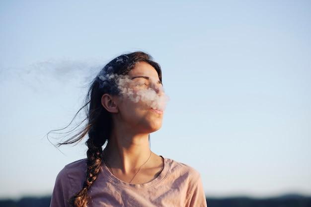 Молодая женщина использует электронную сигарету