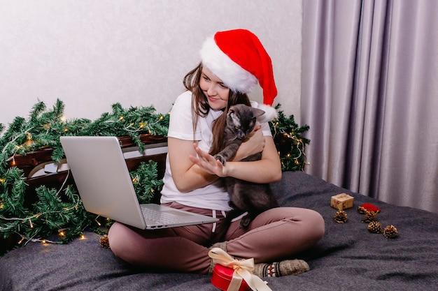 彼女の猫を保持しながら若い女性のビデオ会議