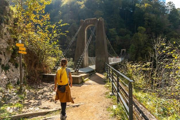 ラローのpasserelleholtzarteを訪れる若い女性。スペインのナバラとピレネーアトランティックの北にあるイラティの森またはジャングルで